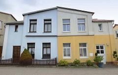 Doppelhaus in der Straße Beim Ausfall in in der Kleinstadt Bützow; die beiden Doppelhaushälften sind unterschiedlich farblich abgesetzt und einer der Vorgärten mit einem Zaun versehen.