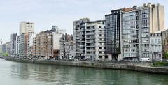 Wohnhäuser am Ufer der Maas in Lüttich / Liège; moderne Hochhäuser und historische Altbauten stehen dicht gedrängt nebeneinander.