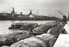 Bis zu fünf Reihen tief liegen die hoch beladenen Schuten am Togokai des Hamburger Südwesthafens. Die Ladung, die aus prall gefüllten Säcken und Tonnen besteht, ist zum größten Teil gegen die Witterung mit Planen geschützt.