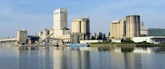 Industrieanlage am Ufer des Albert Kanals in Belgien; Binnenschiffe liegt am Kai.