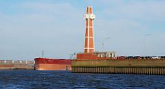Pegelturm mit leerstehendem Flachgebäude an der Einfahrt zum Segelschiffhafen in Hamburg; auf der anderen Seite der Elbe liegt ein Frachtschiff am Kirchenpauerkai.