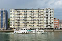 Hochhäuser am Ufer der Maas in Lüttich / Liège. Ein Fluss-Shuttle / La navette fluviale fährt die Maas flussabwärts.
