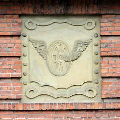 Steinrelief der Eisenbahngesellschaft, Eisenbahnrad mit Flügeln;  Verwaltungsgebäude am Bahnhof in Wismar.