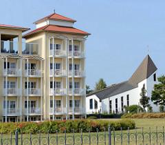 Hotelanlage an der Uferpromenade vom Ostseebad Kühlungsborn; rechts die katholische Kirche der Stadt. Die Kirche Heilige Dreifaltigkeit wurde 2000 geweiht; die Architekten sind Carsten Gieseke und Nicolaus Wöhlk.
