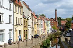 Blick von der Schweinsbrücke in der Hansestadt Wismar auf die Mühlengrube / Mühlenbach und die historischen Wohnhäuser mit unterschiedlich farbige Fassade. Im Hintergrund das historische Gebäude der Stadtmühle, die 1856 errichtet wurde und als Indu