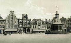 Historisches Motiv vom Marktplatz in der Hansestadt Wismar; im Hintergrund unter anderem das älteste Bürgerhaus Wismars, das Gästehaus alter Schwede. Das Gebäude wurde um 1380 im späten backsteingotischen Stil  errichtet. Rechts der Brunnen der s