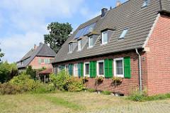 Reihenhäuser mit grünen Holzfensterluken  und Geranienkästen an der Ostseeallee in Boltenhagen.