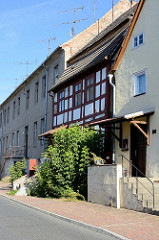 Wohnhäuser in unterschiedlichem Baustil in der Berliner Straße von Oderberg. Ein denkmalgeschütztes Fachwerkgebäude steht eingequetscht zwischen anderen Häusern.