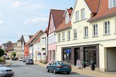 Blick in die Geschäftsstraße / Einkaufstraße lange Straße Bützow; die Hausfassaden sind in unterschiedlichen Farben dekoriert.