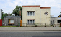 Kubisches Wohnhaus in der Bahnhofstraße von Bützow, daneben ein Holz verkleideter ehemaliger  Ladenraum.