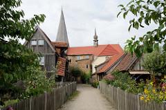 Wohnhäuser / Speicher, teilweise in Holzbauweise mit Vorgarten - im Hintergrund die Stiftskirche von Bützow.