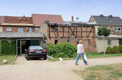 Mit Wellblech gedeckte Garage neben einem verfallenen Fachwerkschuppen am Ufer der Warnow in Bützow.