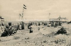 Historisches Foto vom Ostseestrand in Brunshaupten / Kühlungsborn;  Strandkörbe sind aufgestellt - Sandburg mit dem Schriftzug Bergmannsheil.  Touristen stehen  in Straßenkleidung  im Sand, im Hintergrund das Badehaus vom Herrenbad.