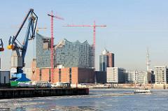 Blick  über das Hamburger Hafenbecken Südwest Hafen im Stadtteil Kleiner Grasbrook zum Ende des Kamerunkais. Auf der anderen Seite der Elbe das fast fertiggestellte Gebäude der Elbephilharmonie.
