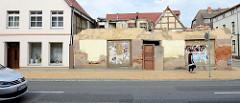 Alt + neu in der Langestraße von Bützow; die Grundmauern eines Eckgebäudes / Hausruine steht neben einem frisch renovierten Wohnhaus.