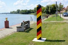 Uferpromenade an der Hohensaaten-Friedrichsthaler Wasserstraße  Gartz / Oder; Grenzpfahl in die deutschen Farben schwarz-rot-gold, dahinter badende Jugendliche.