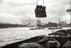 Eine Schute ist mit verpackten Rohrstühlen beladen - eine Ladung der Fracht hängt über dem Schiff am Kran des Kamerunkai vom Hamburger Indiahafen. Im Hintergrund rechts hat ein Frachter vor dem Schuppen 52 des Australiakais festgemacht.