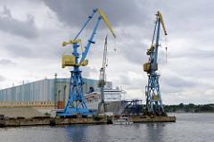 Hafen der Hansestadt Wismar, Blick vom Holzhafen auf Hafenkräne am Kai; dahinter ein Kreuzfahrtschiff vor der Werft Halle. Ein kleines Segelschiff fährt in den Hafen ein.