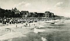 Historische Fotografie vom Strand im Ostseebad Kühlungsborn; der Sandstrand ist dicht mit Strandkörben besetzt - Kinder baden in den Ostseewellen.