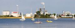 Blick über die Wismarer Bucht zu einem Gewerbegebiet mit qualmenden Schornsteinen, Segelboote auf dem Wasser.