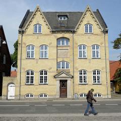 Verwaltungsgebäude mit gelber Ziegelfassade und Doppelgiebel in der Allehelgensgade von Roskilde.