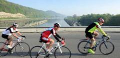 Brücke an der Schleusenanlage bei Lanaye, Belgien - Blick zum Albert Kanal. Rennradfahrer in schneller Fahrt überqueren den Kanal.