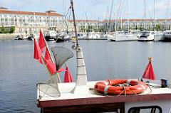 Blick über das Heck eines Fischkutters zur  Ferienanlage mit Marina im Boltenhagener Ortsteil Tannewitz / Weiße Wiek.