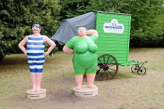 Lebensgroße Kunststofffiguren in historischer Badekleidung sowie ein alter Badekarren stehen an der Strandpromenade von Boltenhagen.