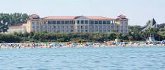 Blick auf den Ostseestrand mit Strandkörben und badenden Touristen in Kühlungsborn; dahinter eine Hotelanlage.
