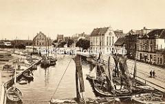 Historische Fotografie vom Fischereihafen in der Hansestadt Wismar; Fischerboote liegen Hafenbecken - im Hintergrund das Backsteingebäude altes Zollhaus.