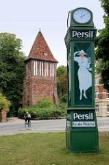 Alte Normaluhr mit der Reklame für das Waschmittel Persil; weiße Frau mit Hut hält eine Packung;  im Hintergrund der historische Wasserturm / Stadttor, der ein Teil der historischen Wehranlage von Wismar ist.