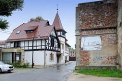Rechts die Rückseite der Schlossruine   von   Groß Strehlitz / Strzelce Opolskie; es ist geplant die Ruine zu restaurieren und ein Agrarzentrum dort einzurichten.  Links eine historische Villa mit Turm und  Fachwerk.