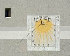 Sonnenuhr mit arabischen und römischen Ziffern an einem Gebäude mit Rauputz in der Stadt Oderberg.