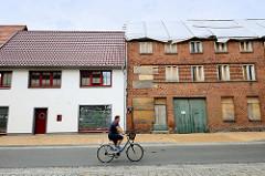 Wohnhäuser in der Schloßstraße / Langestraße  von Bützow; eines der Gebäude ist frisch restauriert und wird bewohnt, das daneben stehende Backsteinhaus hat ein mit Planen abgedecktes Dach und vernagelte Fenster.