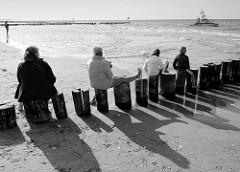 Das Seenotrettungsboot Zander hat freie Fahrt, Touristen am Strand von Zingst beobachten das Geschehen von einer Holzbuhne aus.