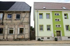 Architektur in der Kleinstadt Bützow,  Mecklenburg-Vorpommern -  ein leerstehendes, renovierungbedürftiges  Fachwerkhaus steht neben einem Wohnhaus mit grün abgesetzter Hausfassade.