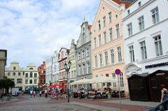 Historische, denkmalgeschützte Architektur am Markt in der Hansestadt Wismar; die Gebäude sind restauriert und haben eine verschieden farbige Fassade -  Restaurants/Café auf dem Marktplatz.
