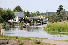 Blick vom ehemaligen Stadthafen von Bützow  auf die Wochenendhäuser am Flussufer, ein kleines Motorboot fährt flussaufwärts.