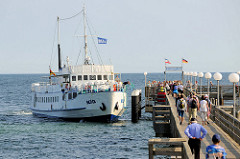Seebrücke von Kühlungsborn, sie wurde 1991 eingeweiht und hat eine Länge von 240 m. Das Ausflugsschiff / Fahrgastschiff Baltica legt gerade an; Touristen warten darauf an Bord zu gehen.