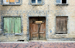 Leerstehendes Wohnhaus mit gelber Backstein-Fassade in der Mantzelstraße  von Bützow. Die verfallene Holztür ist mit Gründerzeit-Schnitzwerk im Türblatt versehen und mit Brettern vernagelt; auch die unteren Fenster sind mit Holzplatten verschlossen.
