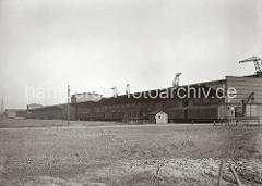 Blick zur Landseite des Verteilungsschuppen 60 - Güterwaggons stehen an der Laderampe des Hafenschuppens. In einer kleinen Bretterbude mit Schornstein ist der Pförtner der Kaiverwaltung untergebracht, ein Schild unter dem Dach weist darauf hin. H