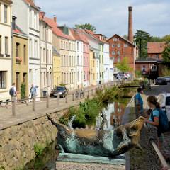 Blick von der Schweinsbrücke in der Hansestadt Wismar auf die Mühlengrube / Mühlenbach und die historischen Wohnhäuser mit unterschiedlich farbige Fassade. Im Hintergrund das historische Gebäude der Stadtmühle, die 1856 errichtet wurde und als Indus