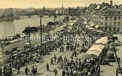 Historische Ansicht vom Maasufer in Lüttich / Liège; Binnenschiffe liegen am Kai - am Ufer findet ein Markt statt.