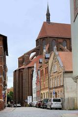 Historische Wohn- und Geschäftshäuser in der Wismarer Straße Hinter dem Chor, dahinter das Kirchenschiff der  Sankt Nikolaikirche.  Die Kirche wurde von 1381-1487 als Kirche der Seefahrer und Fischer erbaut. Sie gilt als Meisterwerk der Spätgotik un