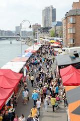 Flohmarkt am Ufer der Maas in Lüttich / Liège; Marktstände mit Zeltdach, Passanten schlendern über den Markt.