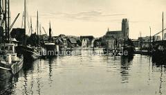 Historisches  Bild vom Fischereihafen der Hansestadt Wismar; Fischkutter liegen am Kai - im Hintergrund der Kirchturm der Sankt Marienkirche.