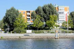 Uferpromenade an Hohensaaten-Friedrichsthaler Wasserstraße in Schwedt  (Oder); mehrstöckige Wohnblocks mit Blick auf den Kanal.