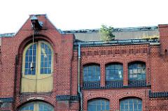 Historische Industriearchitektur, Fabrikgebäude der New-York Hamburger Gummi-Waaren Compagnie in Hamburg Harburg.  Dachwinde mit Eisenhaken am Giebel eines Lagergebäudes - eine kleine Kiefer wächst in der Regenrinne des Backsteinspeichers.