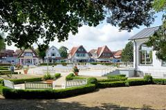 Blick von der Strandpromenade Boltenhagen auf den Kurpark und die historische Häuserzeile an der Mittelpromenade.