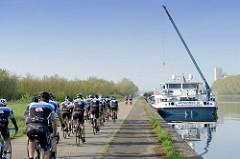 Binnenschiff am Kai des Albert Kanals in Belgien - der Hebekran für das Kfz ist ausgefahren und das Fahrzeug an Land gebracht. Eine Gruppe Rennradfahrer fahren entlang des Kanals Richtung Lüttich.